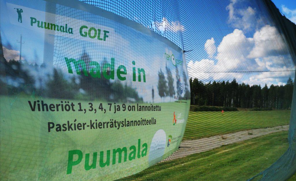 """mainos Puumala Golfin viheriöltä, jossa lukee """"made in Puumala. Viheriöt 1, 3, 4, 7 ja 9 on lannoitettu Paskíer-kierrätyslannoitteella"""". Takana golfkenttää ja metsää."""